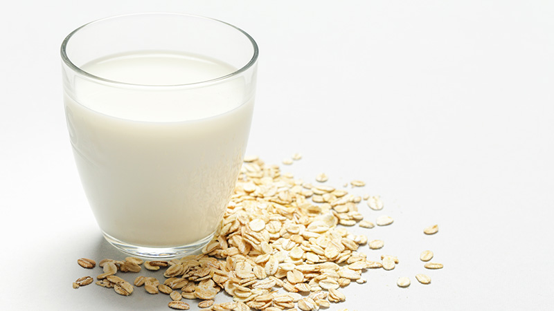 A glass of oat milk next to rolled oats.