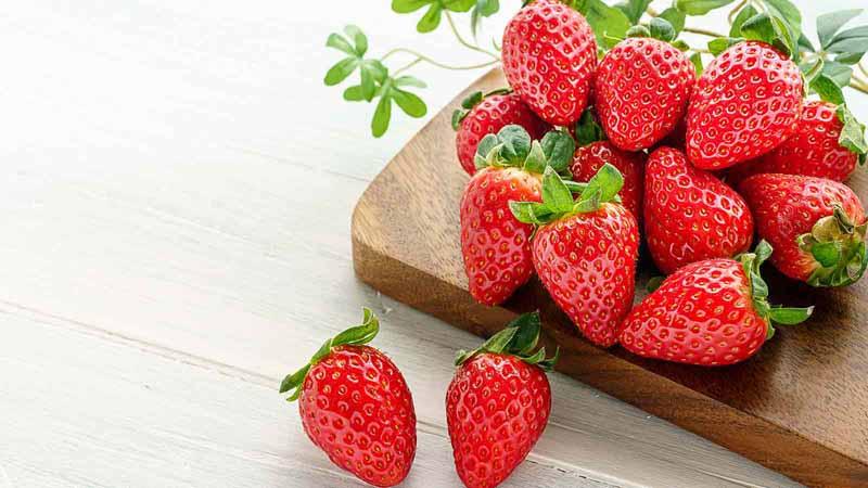 Fresh strawberry isolated on wooden background.