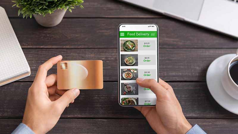 Person using a credit card to purchase food on a smartphone.