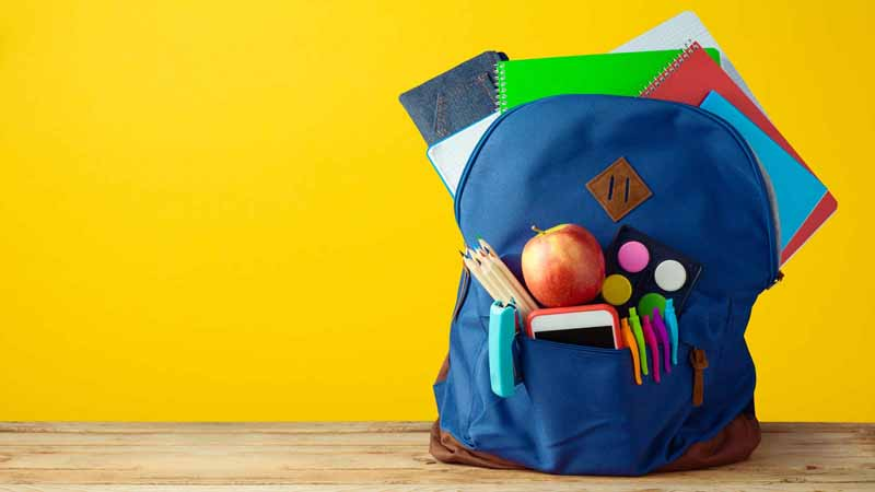A backpack stuffed with various school supplies.