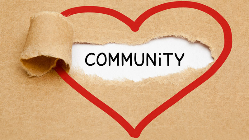 The word 'community' appearing behind ripped paper within a red heart.