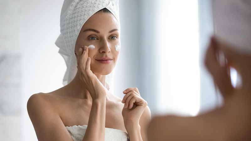 A woman applying face moisturizer in the mirror.