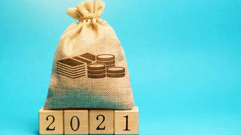 "A bag of money on top of wooden blocks that say ""2021."""