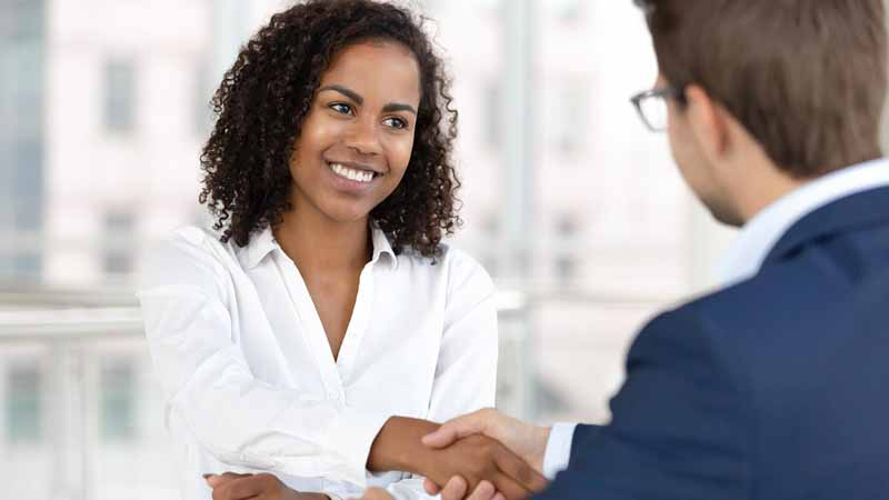 Two businesspeople shaking hands at a desk.