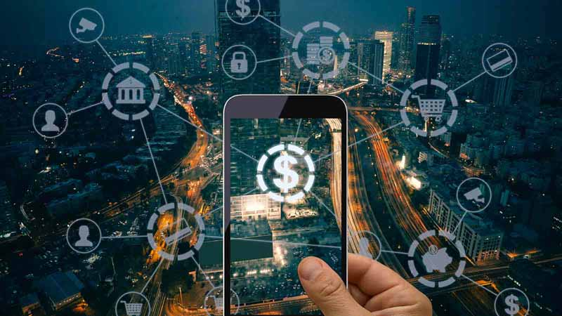 Hand holding smartphone on busy city background with abstract financial graphics.