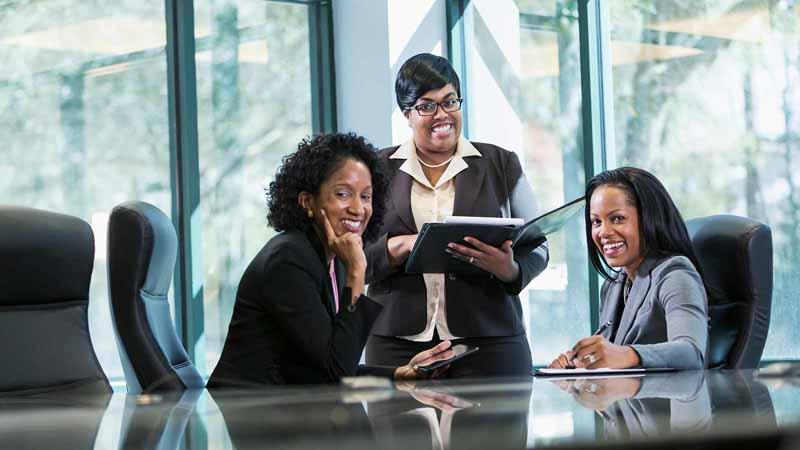 Three Black female entrepreneurs having a meeting.