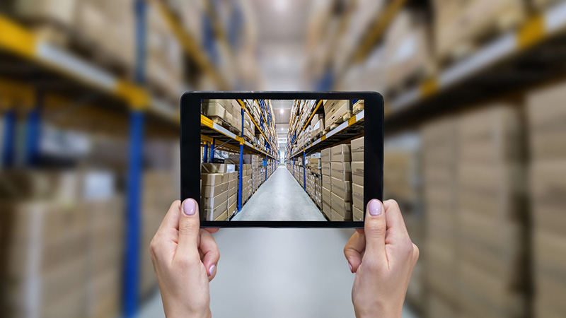 A person holding a tablet in a warehouse.