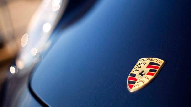 Porsche logo on hood of car.