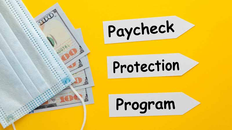 Paycheck Protection Program written next to surgical masks and money.