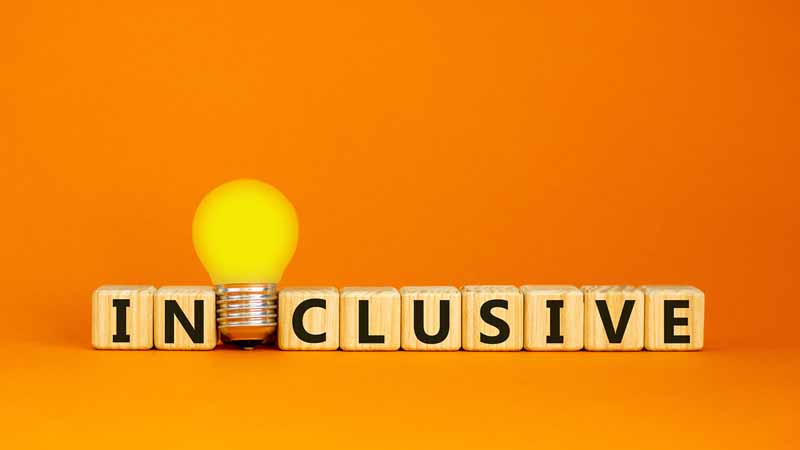 A lightbulb and wooden cubes that spell out 'inclusive.'