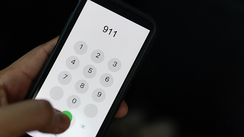 Hand holding a smartphone set to dial 911.