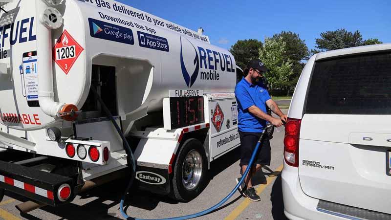 A ReFuel Mobile truck refueling a van.