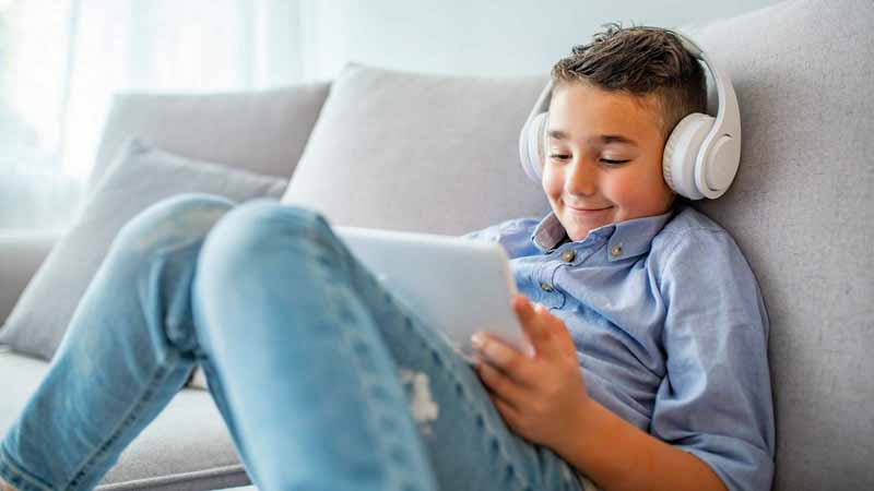A boy playing video games on a tablet.