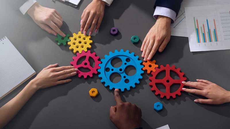 Group of people combining gear parts on a table