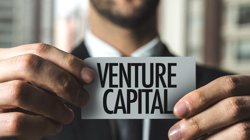 Businessman holding 'venture capital' sign.