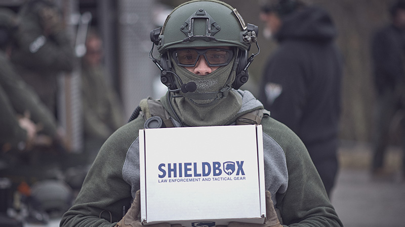Person in tactical gear holding a ShieldBox box.