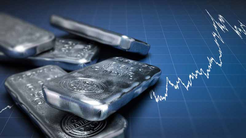 Silver bullion bars on top of a rising chart.