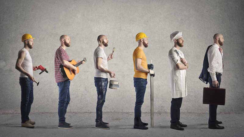 A man dressed as a construction worker, musician, chef, and office worker.
