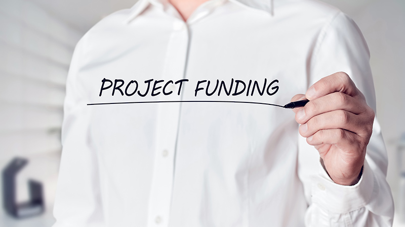 Businessman writing 'Project Funding' on a virtual screen.