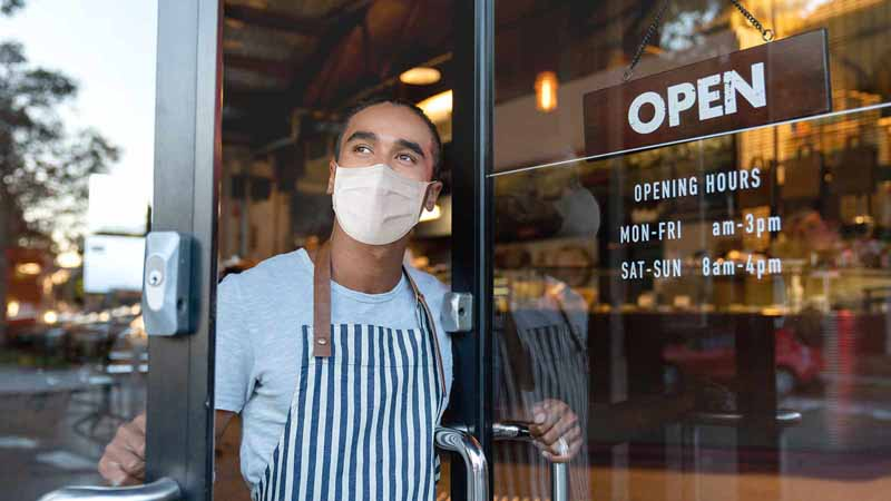 Business owner opening the door at a cafe wearing a face mask.