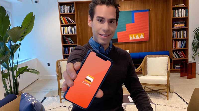 S'More founder Adam Cohen-Aslatei showing phone app on smartphone