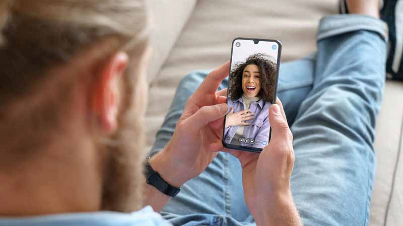 Man watching a video of a woman on an app.