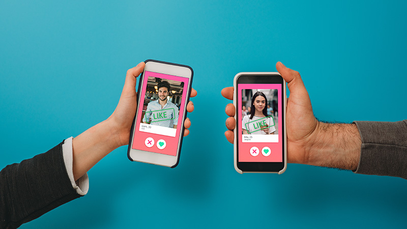 Two people holding up smartphones that show a dating app.