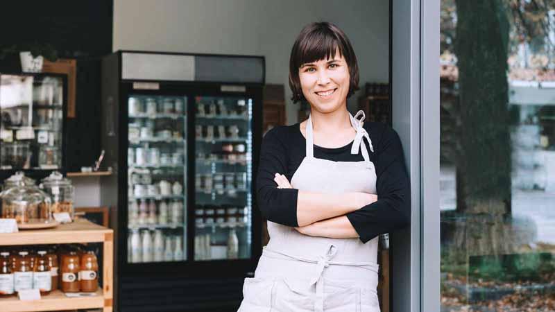 Businesswoman standing in the doorway of her small business.