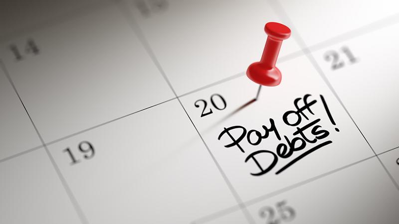 Calendar with a thumbtack over a 'pay off debts' entry.