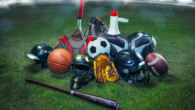 A pile of sports equipment on a sports field.