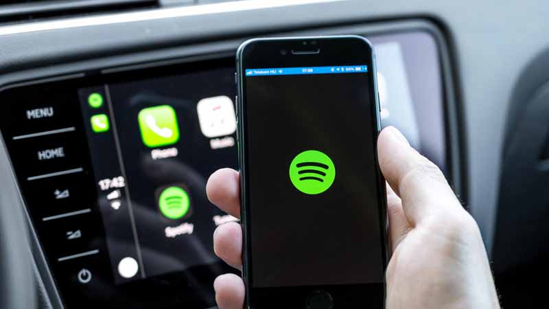 A person using Spotify on their smartphone in their car.
