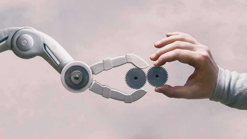 A robot hand and human hand holding up gears.