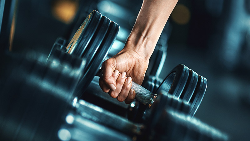 Closeup side view of woman grabbing a dumbbell from a dumbbell rack.