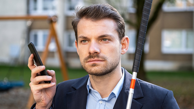 A blind man holding a walking cane and a smartphone.