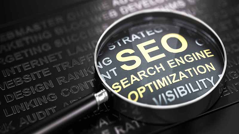 Magnifying glass highlighting 'search engine optimization.'