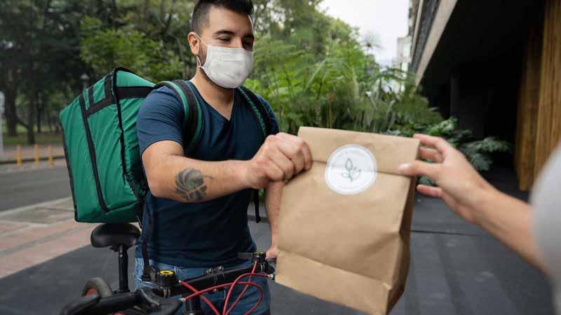 A courier delivering food on a bike.