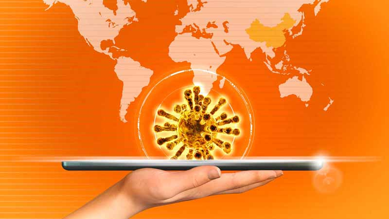 Hand holding tablet projecting coronavirus in front of a world map.