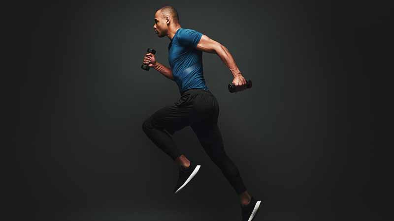 A man running with dumbbells in his hands.