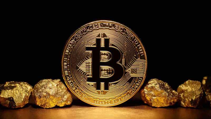 Bitcoin coin next to gold nuggets.