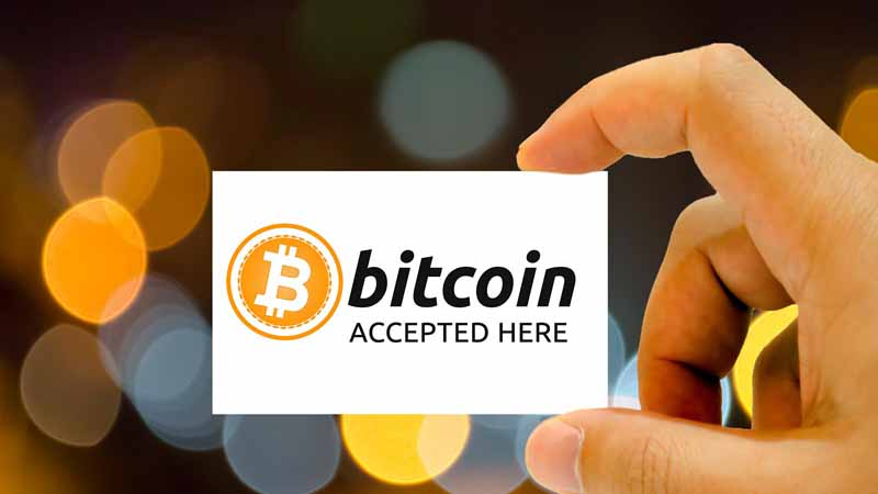"""Person holding """"Bitcoin accepted here"""" sign."""