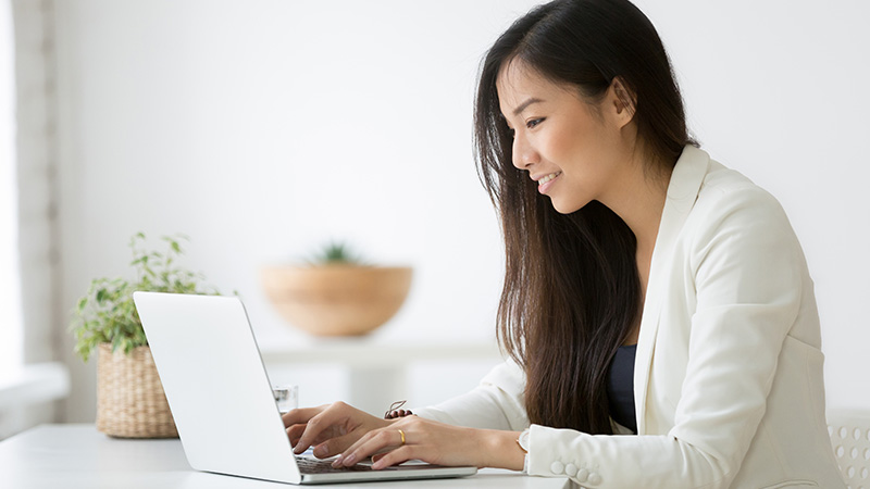 A young woman writing on her laptop.