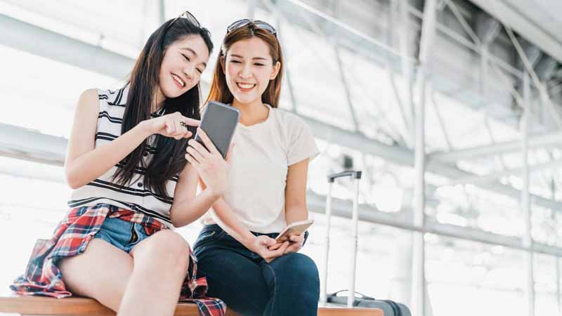 Two Asian women watching a video on a smartphone.