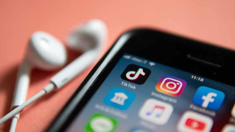 TikTok app on iPhone next to headphones.