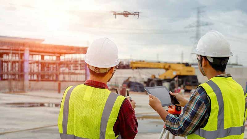 Construction workers piloting a drone
