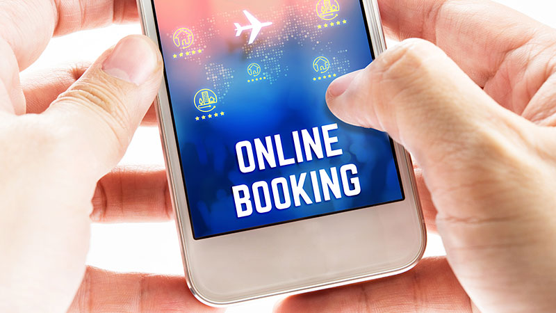Hands holding a smartphone that says 'online booking.'