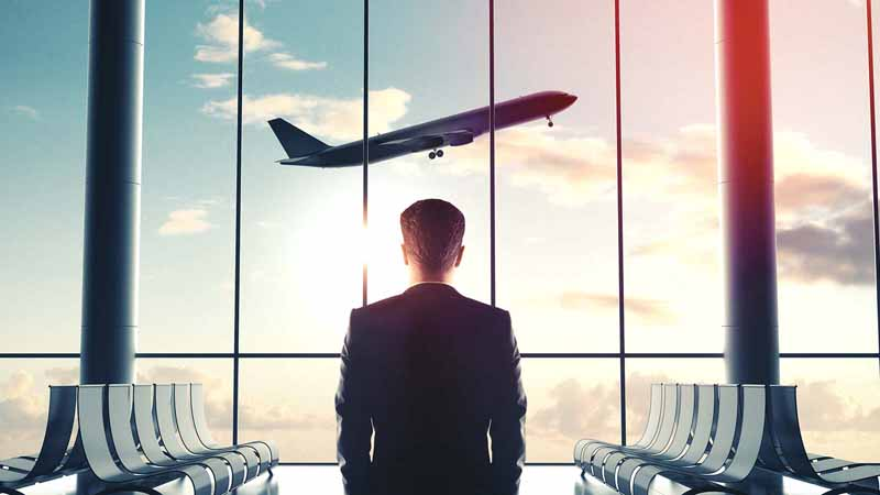 Businessman in an airport watching an airplane take off.