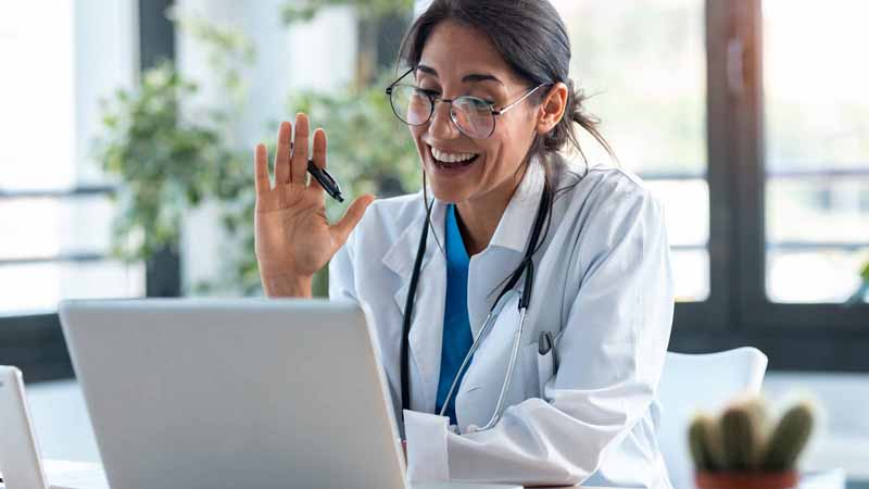 A doctor waving to her laptop screen.