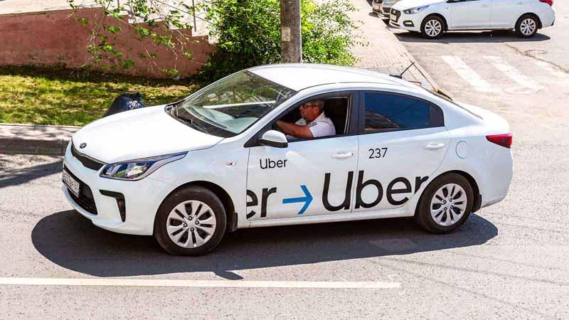 An Uber taxi driving through a city.