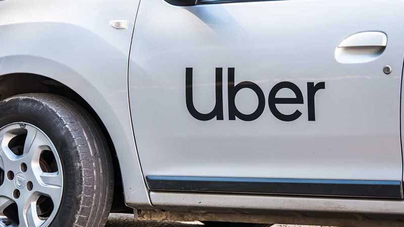 A car with the Uber logo on the driver-side door.
