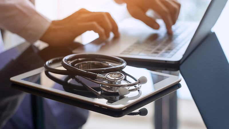 Doctor working on a laptop next to a stethoscope.